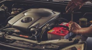 Hands using a tool on a part underneath the hood of a vehicle