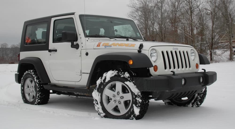 White 2010 Jeep Wrangler Islander in snowy field