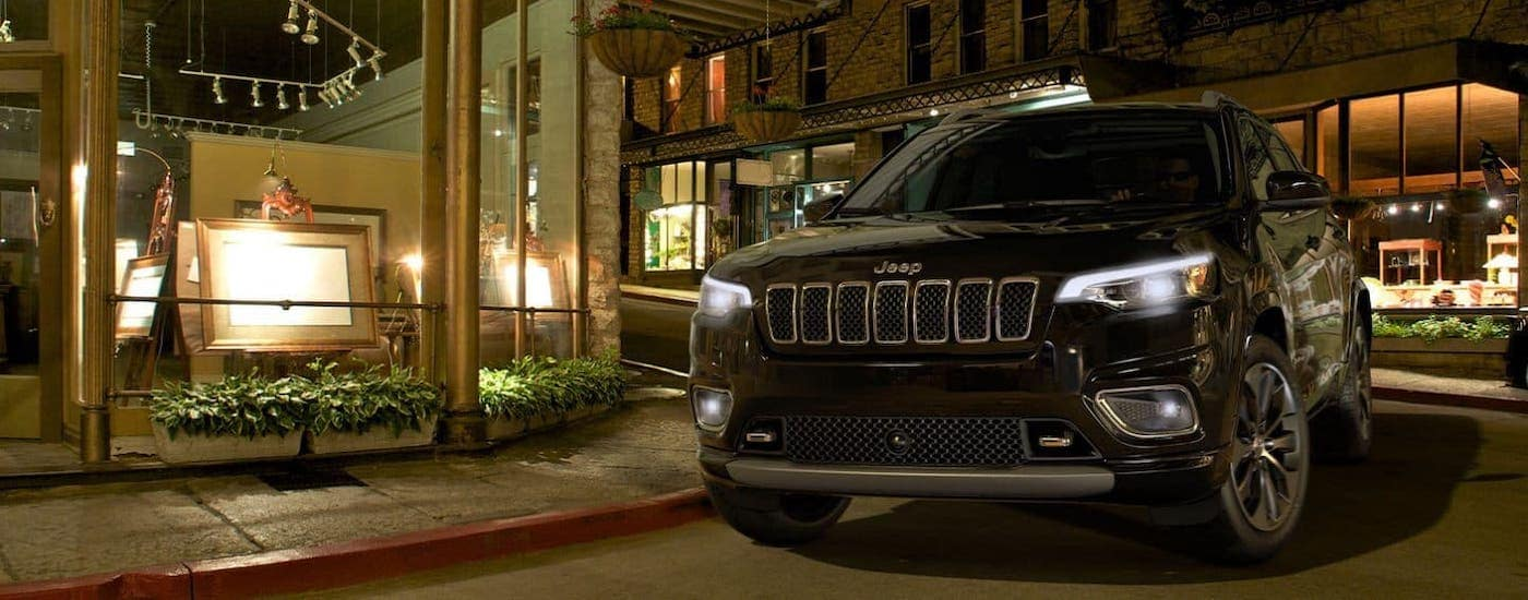 A popular used car in Colorado Springs, a black 2019 Jeep Cherokee is parked in front of an art gallery at night.