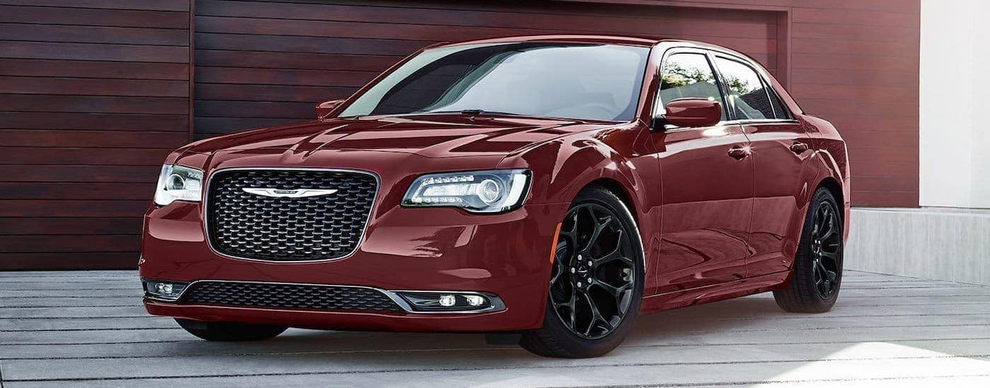 A red 2019 Chrysler 300 is parked in front of a red/brown wooden garage in Colorado Springs, CO.