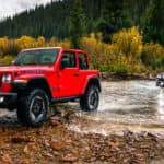 A red Jeep Wrangler leads the way in crossing a Colorado Springs river