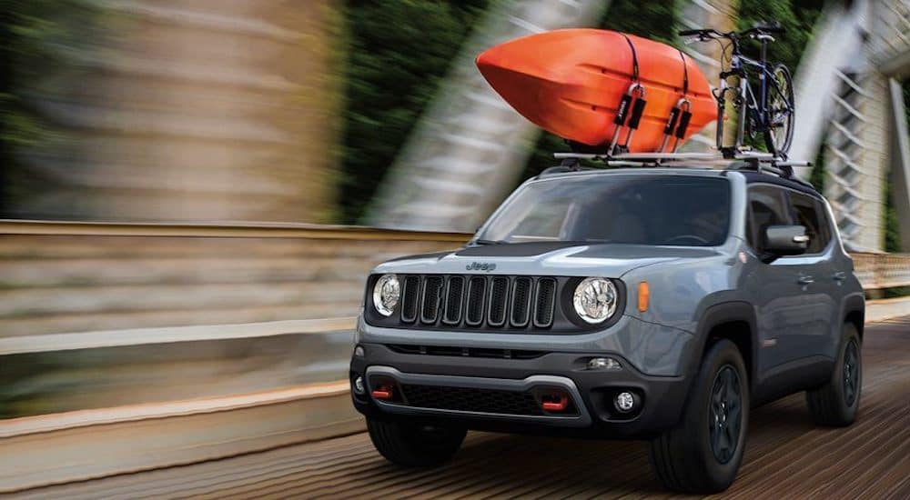 A silver 2018 Jeep Renegade crossed a bridge with a kayak on the roof