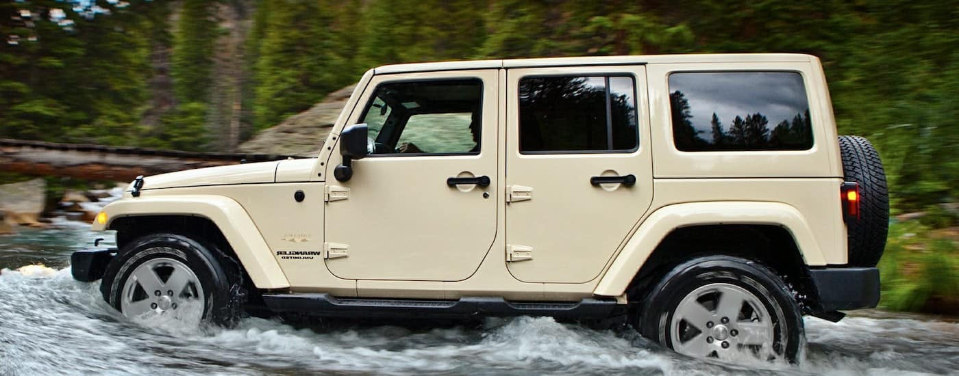 A tan Jeep wrangler navigates a stream in Colorado Springs