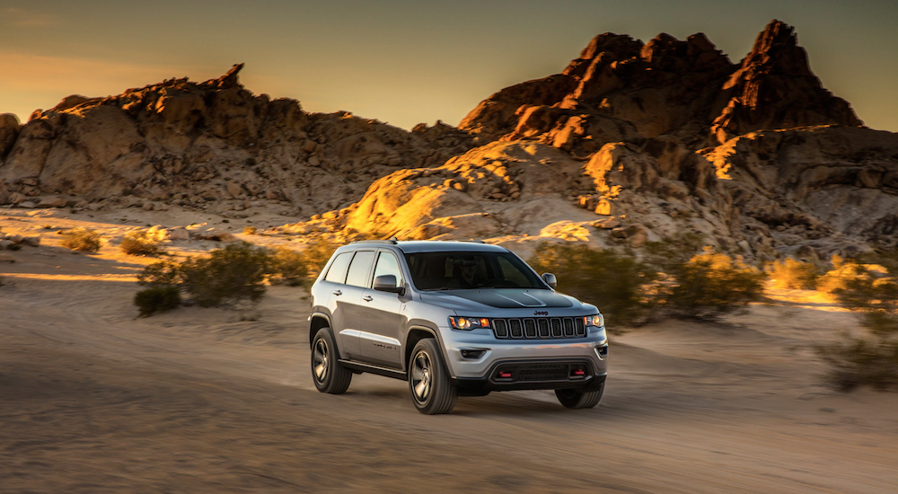 A Silver Jeep Grand Cherokee cruises down a dusty desert road in Colorado Springs