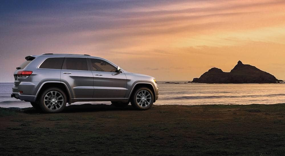 Silver 2018 Jeep Grand Cherokee at beach at sunset