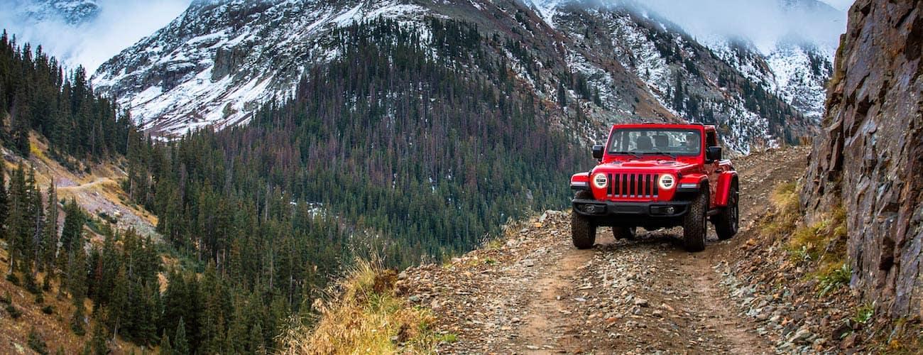 Red 2019 Jeep Wrangler JL on mountain road near Colorado Springs