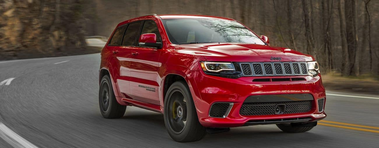 Red 2019 Jeep Grand Cherokee rips down a twisty Colorado road