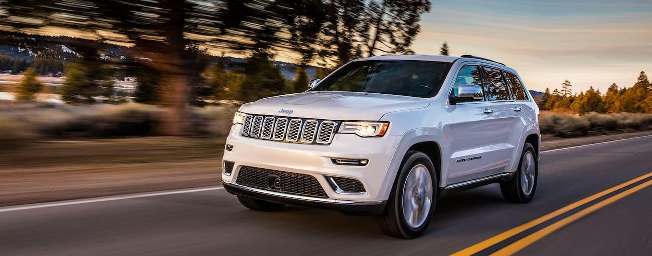 A white 2019 Jeep Grand Cherokee drives down a country road at dusk in Colorado Springs, CO