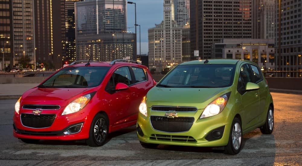 Red and Green 2015 Chevy Spark in city