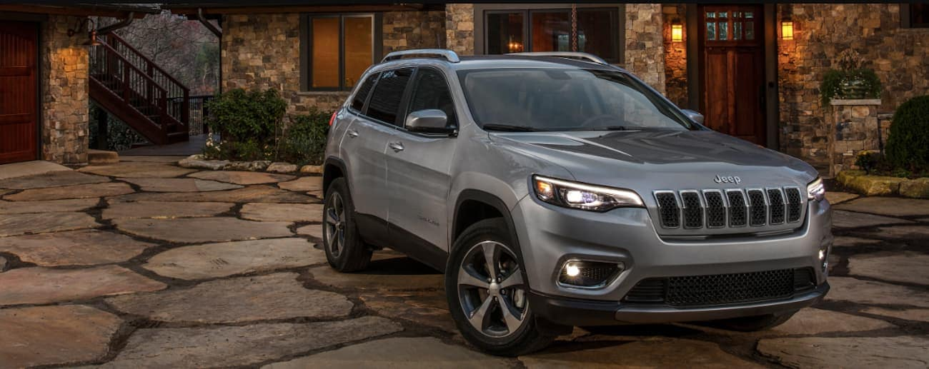 Colorado Springs - A dark gray 2019 Jeep Cherokee parked outside of an upscale home