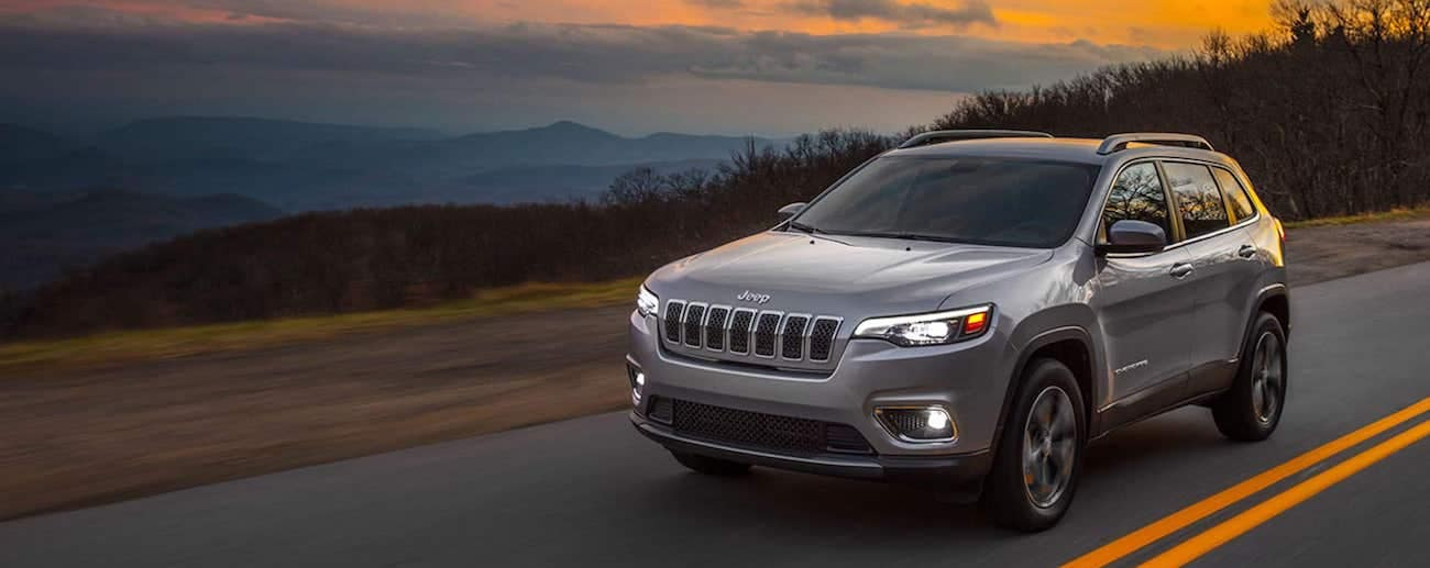 Colorado Springs - A silver 2019 Jeep Cherokee drives an empty highway at dusk