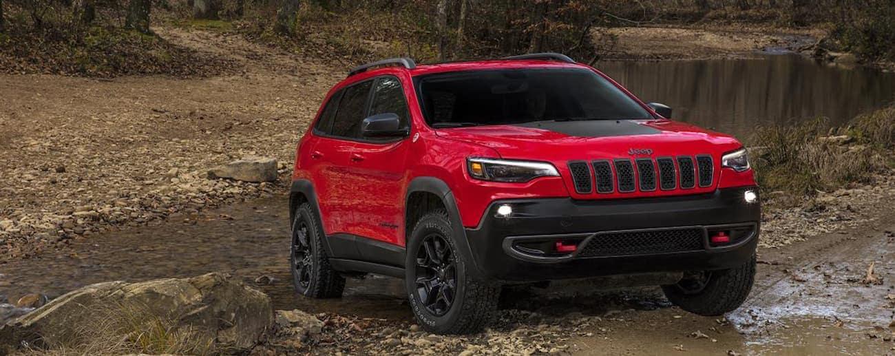 Colorado Springs - A bright red 2019 Jeep Cherokee navigates a sandy path