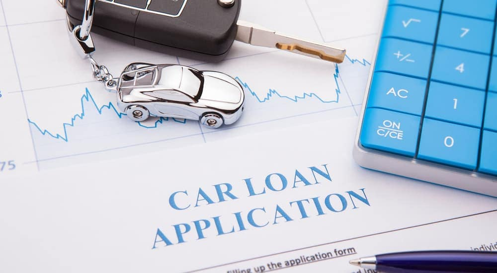 Car loan application, car key and car keychain, calculator