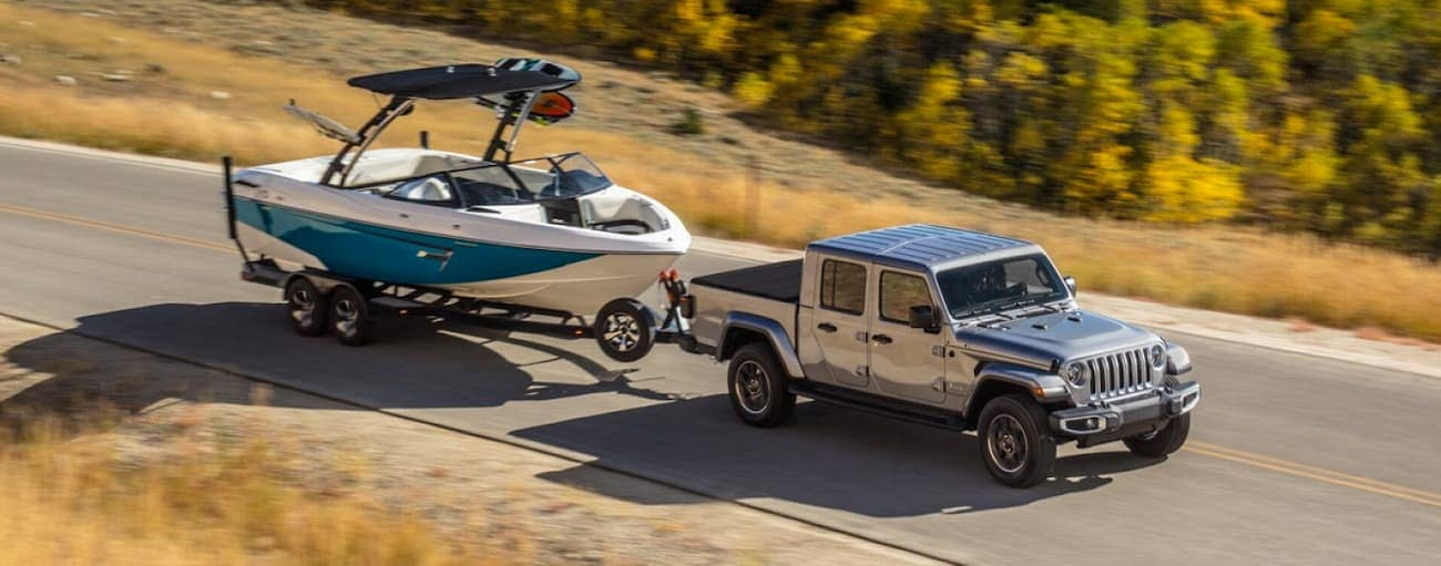 A grey 2020 Jeep Gladiator is towing a boat outside Colorado Springs, CO.