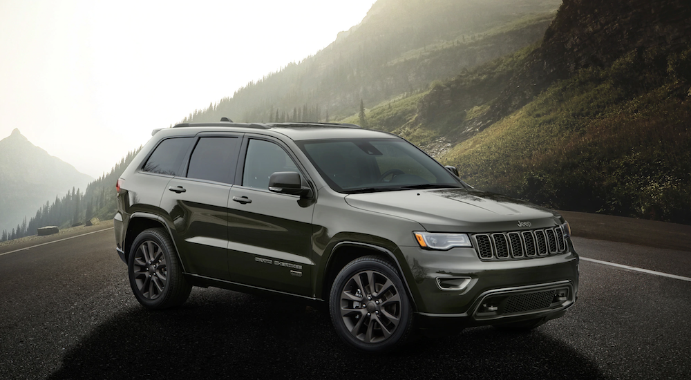 A dark gray certified pre owned Jeep Grand Cherokee on a dark and foggy mountain road