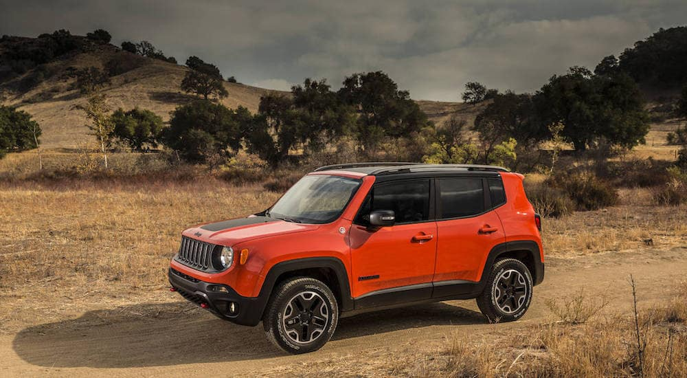 A bight orange certified pre-owned Jeep Renegade a dusty and brown mountain landscape