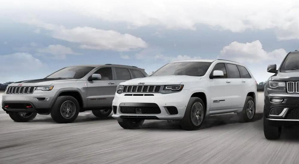 A trio of black, white, and gray high performance Jeep models race across a wide road near Colorado Springs.