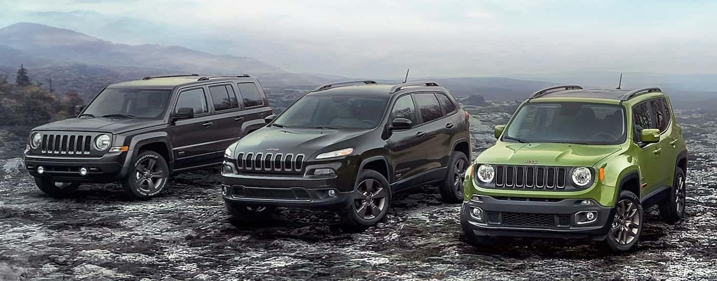 A trio of black and green Jeep models are parked on a bleak and rocky background.