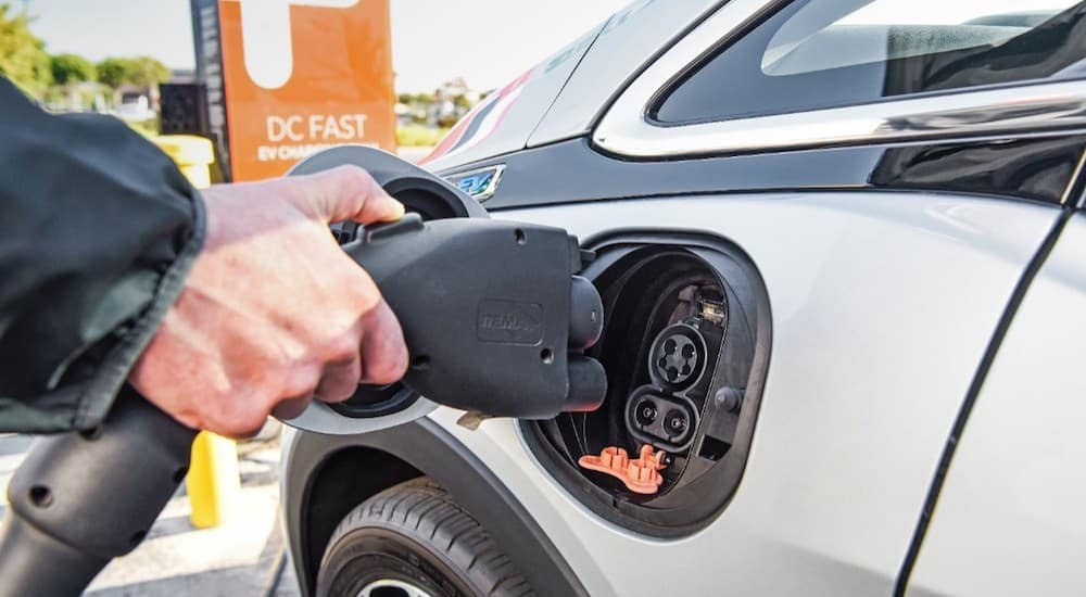 A hand plugs in a Chevy Bolt EV