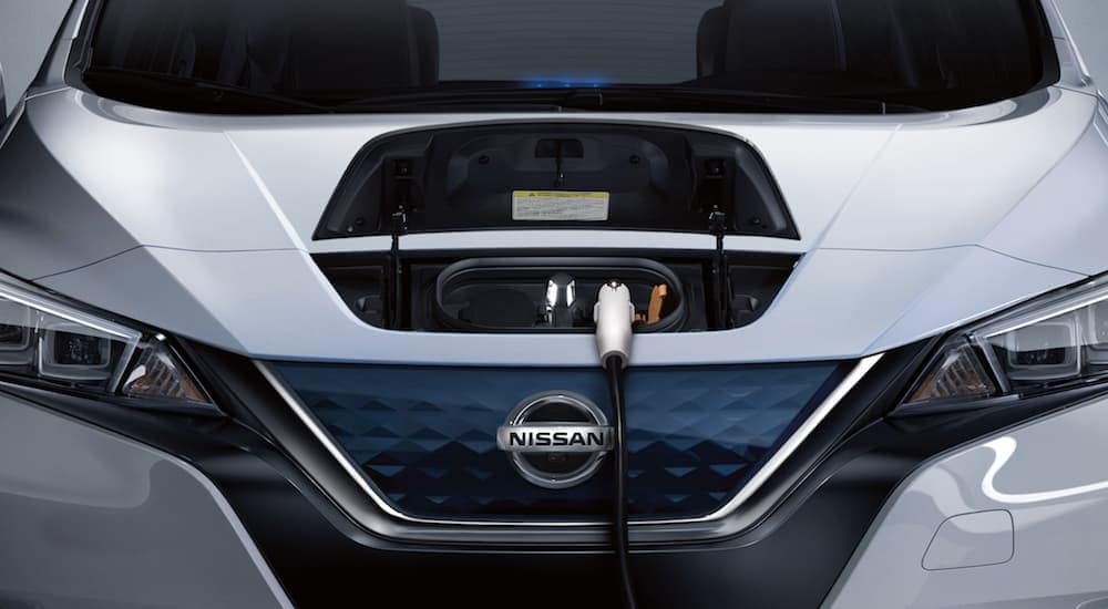 A plug hanging from the front of a Nissan Leaf