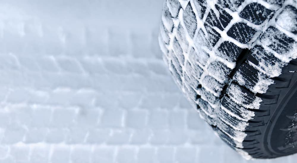 A closeup of a winter tire with snow