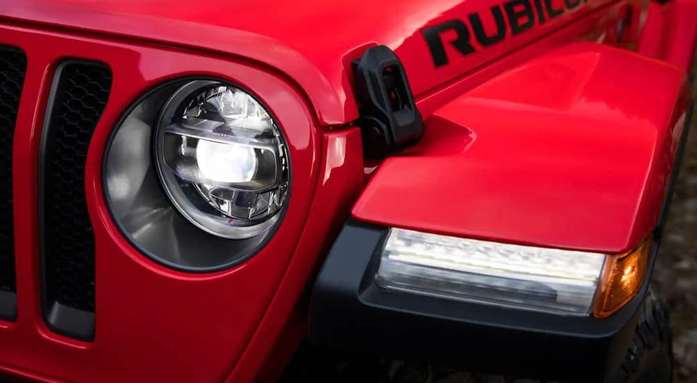 A closeup of the headlight on a red 2019 Jeep Wrangler Rubicon