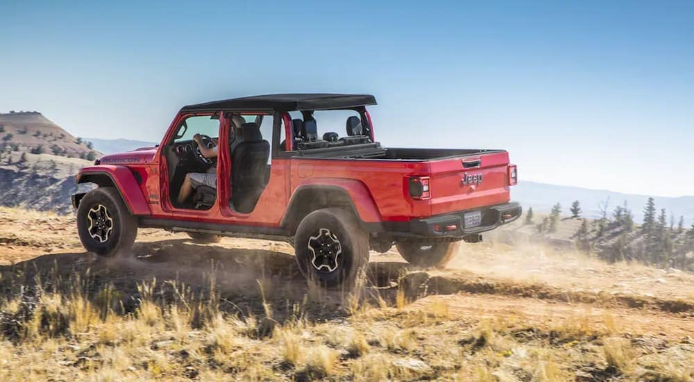 A red 2020 Jeep Gladiator driving on a mountain with the doors off