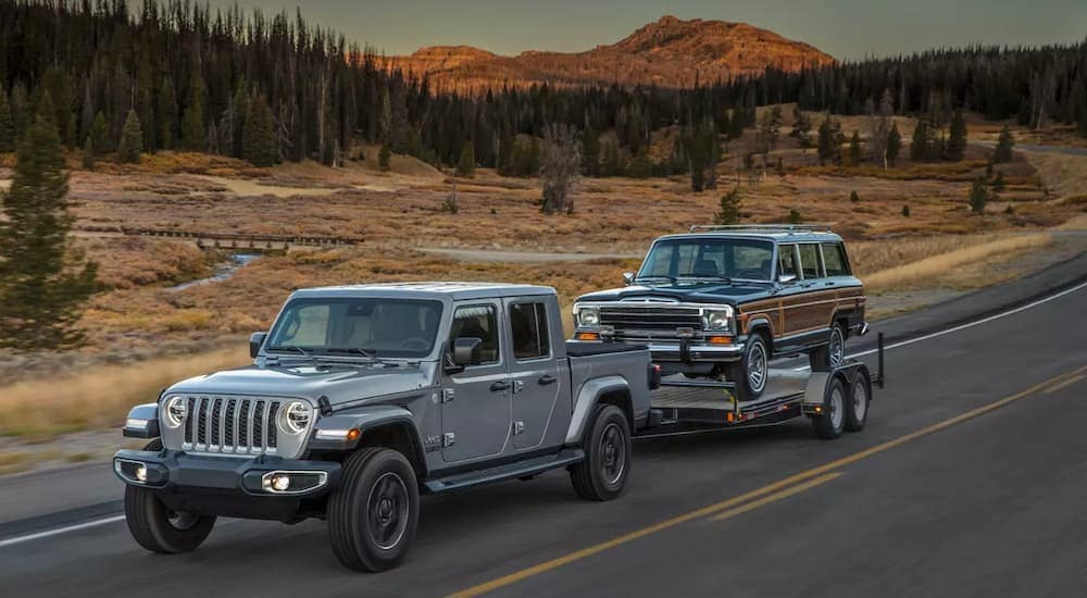 A gray 2020 Jeep Gladiator towing a classic Jeep Wagoneer
