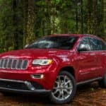 A Certified Pre Owned red 2015 Jeep Grand Cherokee is parked in the woods.