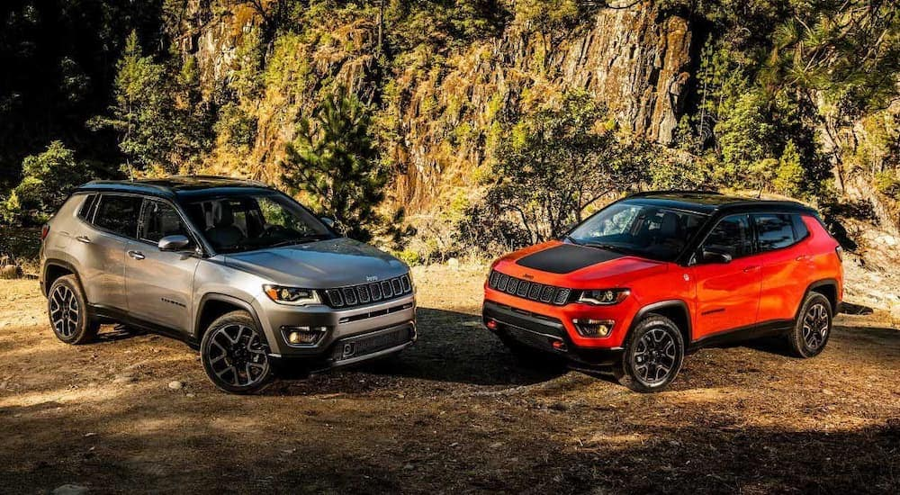 a silver 2018 Jeep Compass is parked next to an orange one with rock face behind them.