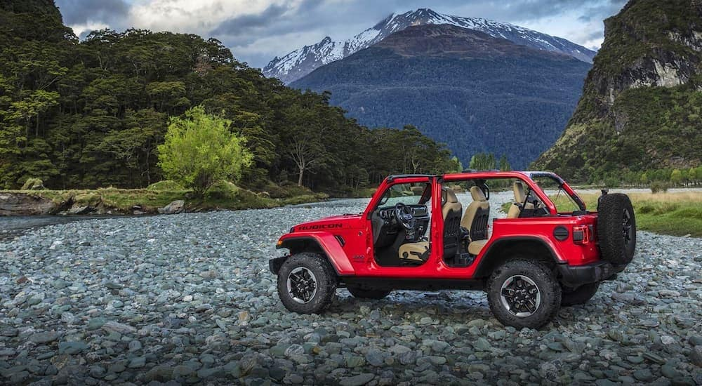 A red 2019 Jeep Wrangler has the top and doors of and is parked on rocky ground with mountains in the distance. Check one out at a Jeep dealership in Colorado Springs.