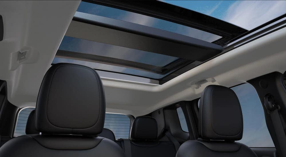 The black and white interior of a 2019 Jeep Renegade is shown featuring the sun roof.