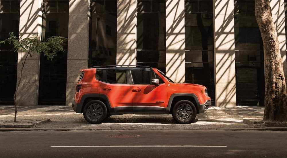 An orange 2019 Jeep Renegade is parked outside a building on a shady street. Check one out at a Jeep dealership in Colorado Springs.