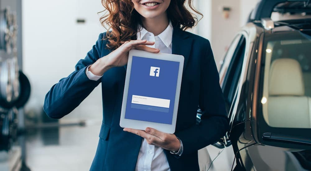 A woman in a suit is holding a tablet with the Facebook login page displayed.