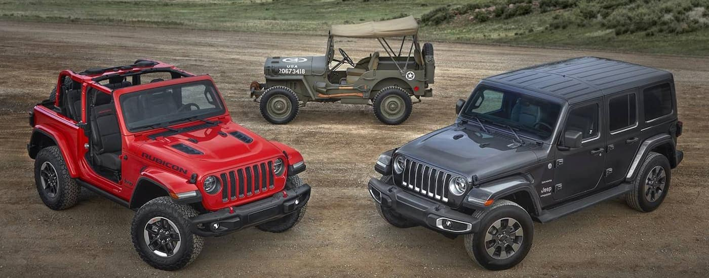 A red Wrangler Rubicon, a gray Wrangler Unlimited 4-door Sahara and a military Jeep Willys are parked in a field.