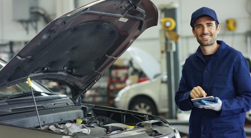 A mechanic is smiling after going over a list to check on a Certified Pre-Owned vehicle.