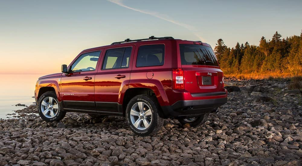 A red 2017 Jeep Patriot is on a rocky lake shore where you can similar used cars in Colorado Springs, CO.