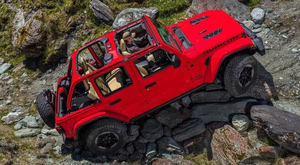 A red 2018 Jeep Wrangler is rock crawling after leaving the dealership where you can find similar used cars in Colorado Springs, CO.