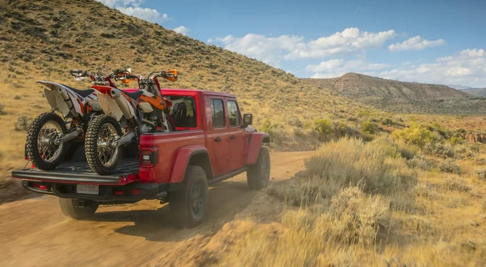 A red 2020 Jeep Gladiator with dirt bikes in the bed is off road headed to Colorado Springs, CO.