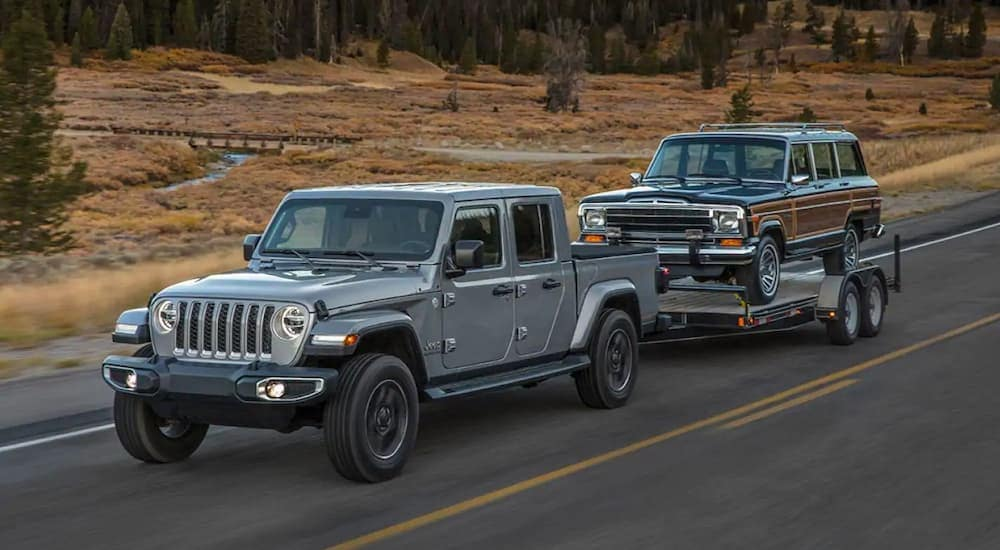 A grey 2020 Jeep Gladiator is towing a Jeep Wagoneer near Corsicana, TX. Check out power when comparing the 2020 Jeep Gladiator vs 2019 Chevy Colorado.