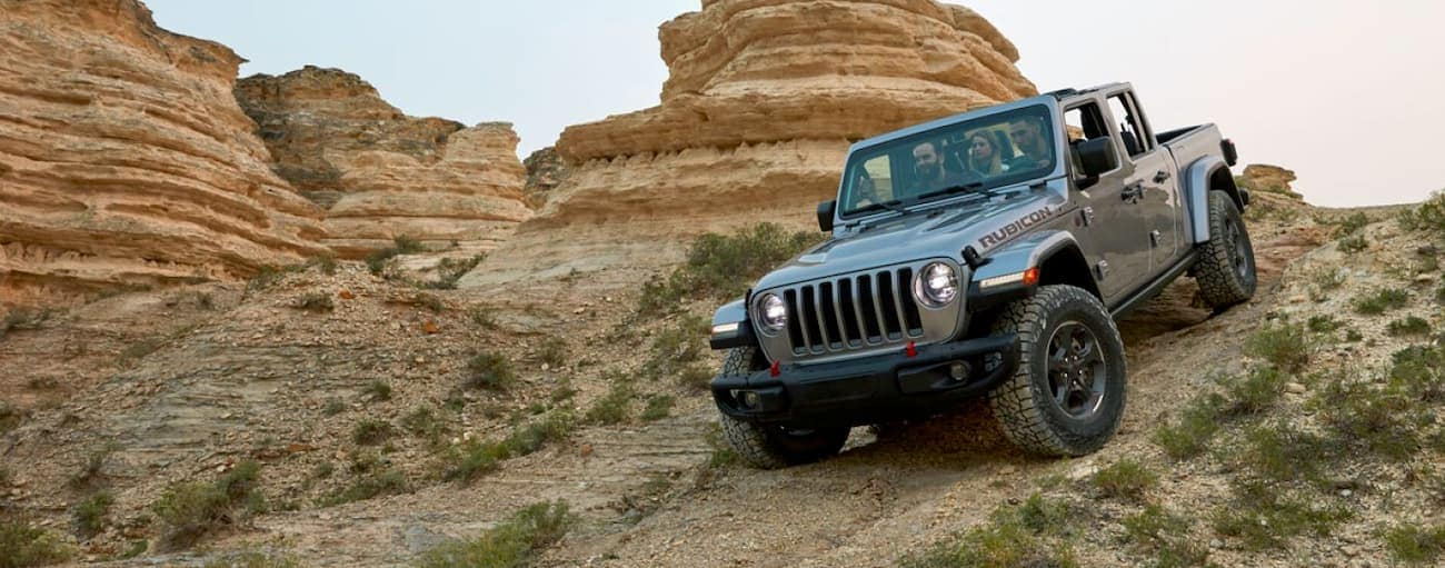 A grey 2020 Jeep Gladiator, which wins when comparing the 2020 Jeep Gladiator vs 2019 Chevy Colorado for off-road capability, is driving down a hill on a trail in the desert.