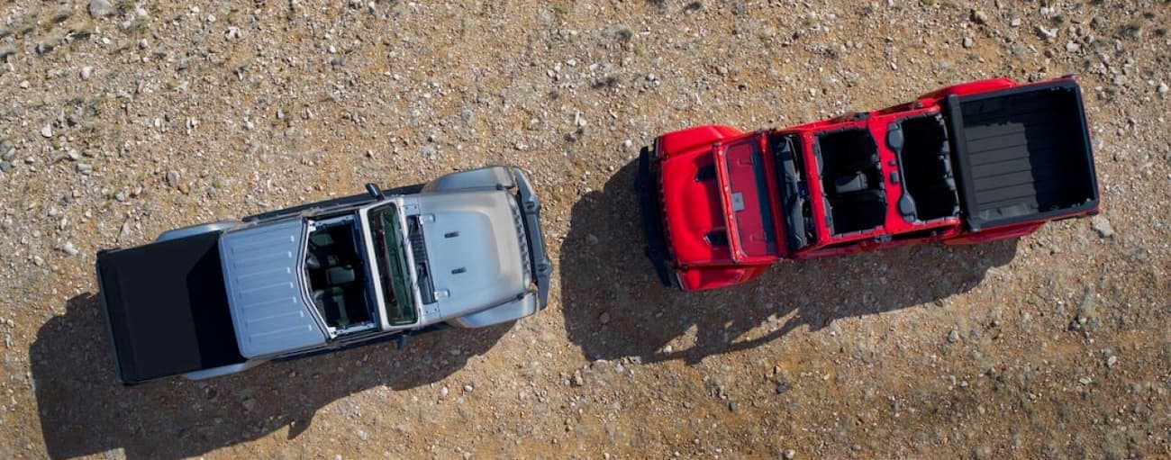Two configurations for the 2020 Jeep Gladiator, in red and grey, are shown from above in a dirt area near Colorado Springs, CO.