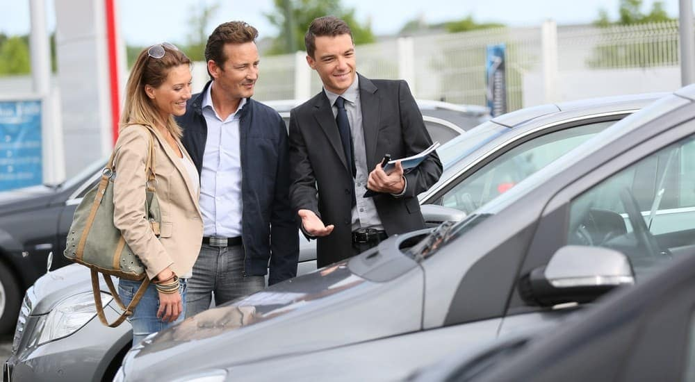 A no haggle car dealer showing a vehicle to a man and woman