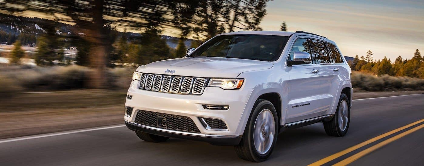 2019 Jeep Grand Cherokee driving on a road going to a Jeep dealership in Denver, CO