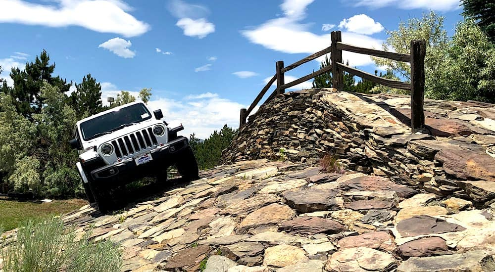 A white Jeep Wrangler is next to the stone bridge on the Faricy Test Track in Colorado Springs, CO.