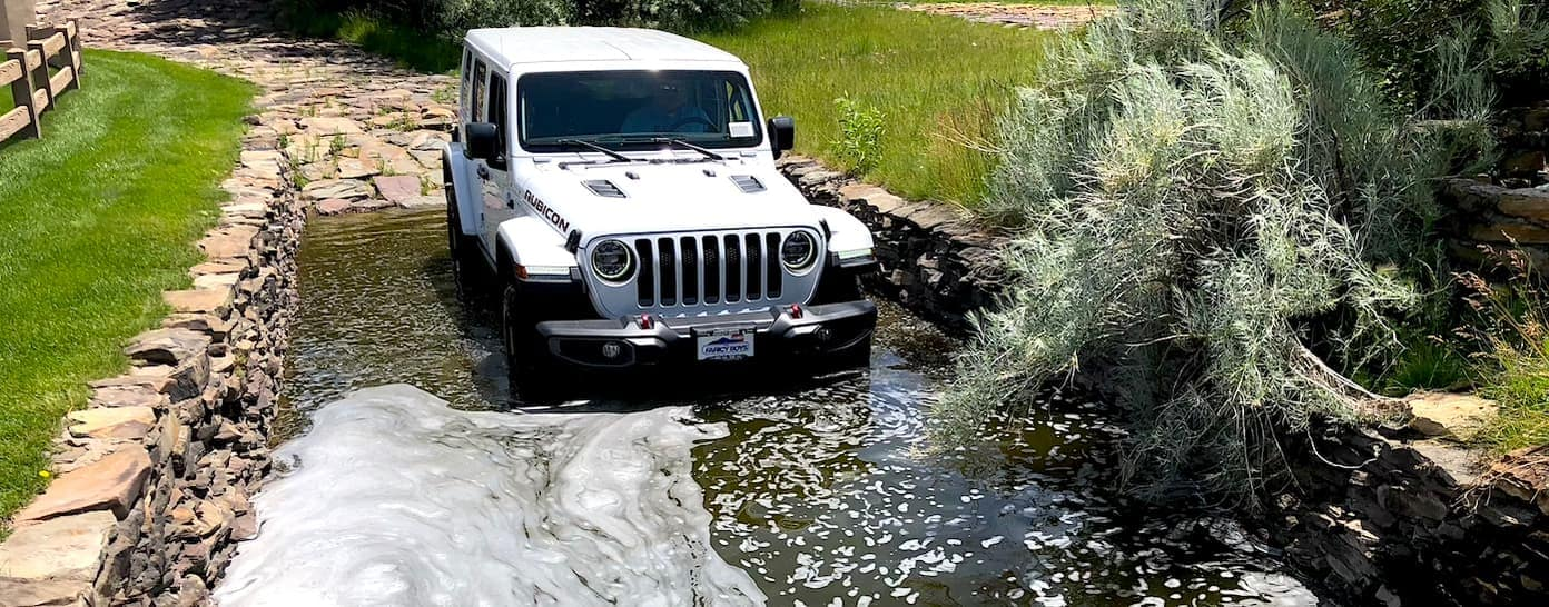 A white Jeep Wrangler is doing the water crossing at the Faricy Test Track.