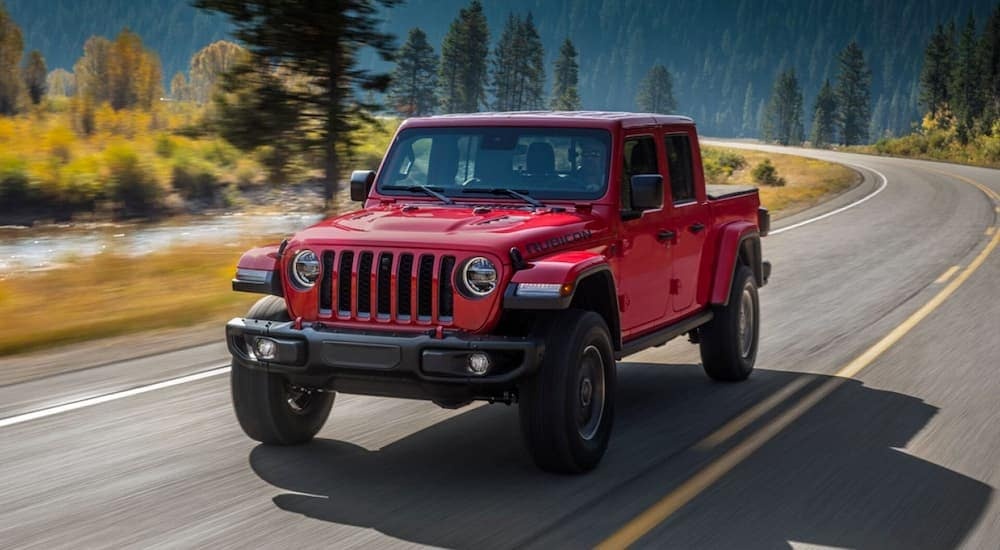 A red 2020 Jeep Gladiator is driving past mountains after leaving a Jeep dealership near me.
