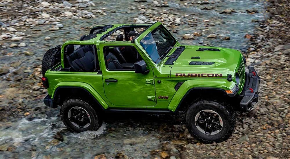 A green 2019 Jeep Wrangler is crossing a rocky stream near Colorado Springs, CO.
