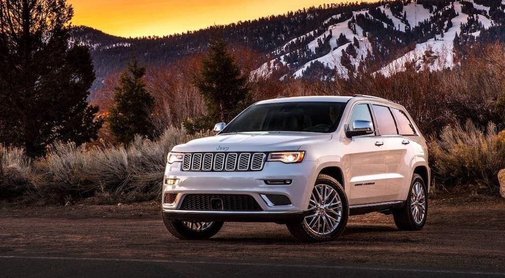 A white Jeep Grand Cherokee parked in front of a mountain, used SUVs for sale, with a sunset