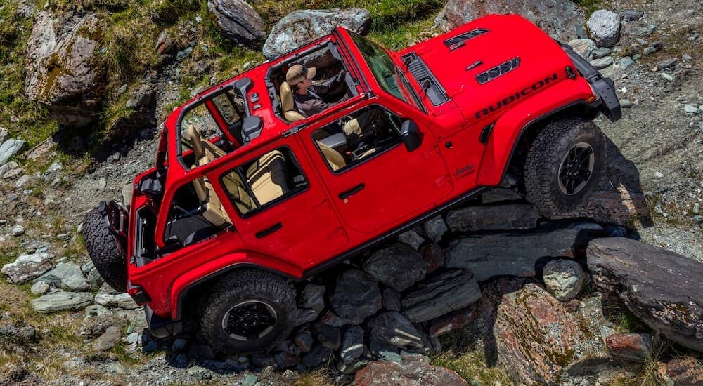A red 2018 Jeep Wrangler is climbing a rocking off-road trail.